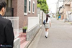 Student Walking Along Street In Uniform Long Hair In Ponytail
