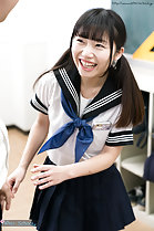 Standing in classroom pigtails falling over her uniform beaming smile