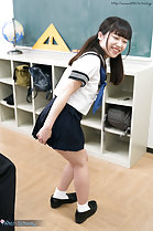 Bending over in classroom wearing uniform hand on uniform skirt