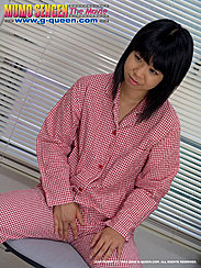 Japanese Teen Ran Amami Seated In Front Of Blinds Wearing Check Pyjamas Hand Resting Between Her Legs