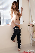 Sitting on window sill coloured long hair covering left small breast in white panties jeans and high heels