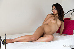 Sitting On Bed Stretching Out Long Hair Hand On Her Breast