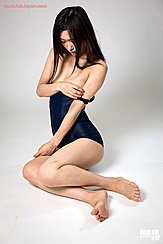 Yamada Reika Seated Long Hair Over Her Shoulders Removing Strap Of Her Swimsuit From Her Shoulder Bare Feet