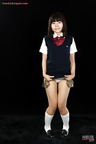 Kogal raising the hem of her uniform skirt knees pressed together wearing socks and shoes